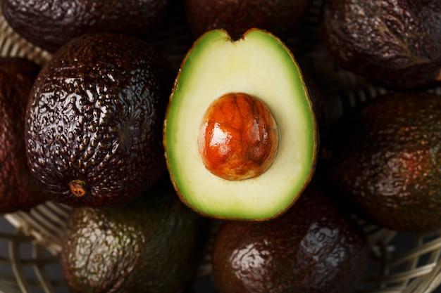 Avocats mûrs dans un panier sur une table noire, avec un fruit coupé et une pierre. macro, gros plan