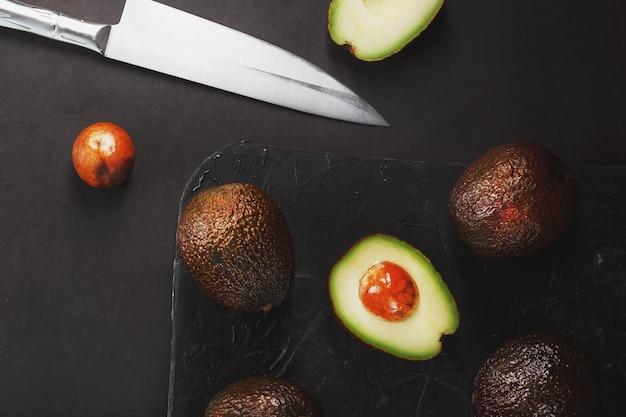 Les avocats mûrs dans un panier sur une table noire, avec un fruit coupé et une pierre