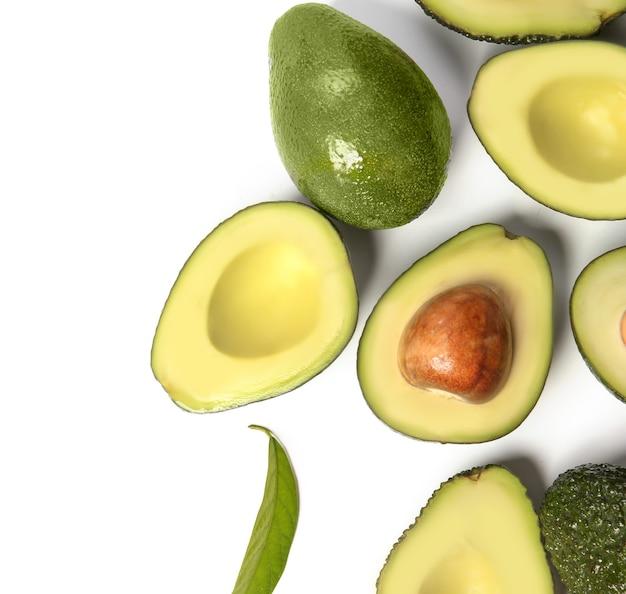 Avocats mûrs frais sur une surface blanche, vue du dessus