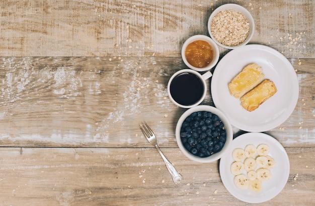 L'avoine; confiture; café; myrtilles; tranche de banane et pain grillé sur une planche en bois
