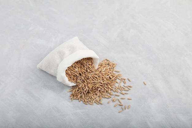 Avoine à grains entiers renversée du sac sur fond gris