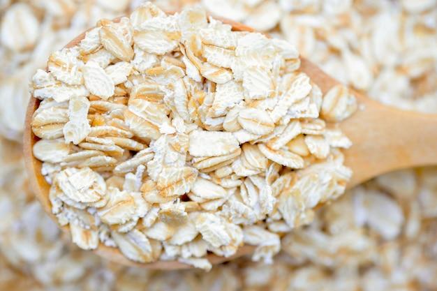 L'avoine roulée en gros plan dans une cuillère en bois sur un tas d'avoine roulée est un aliment sain à grains entiers