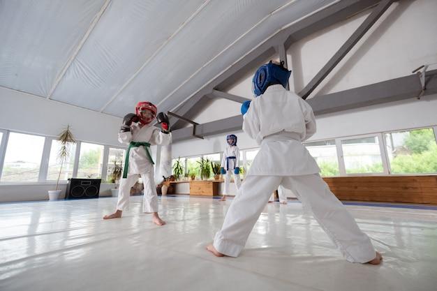 Avoir la bataille. garçons étudiant les arts martiaux se battant avec des casques et des gants