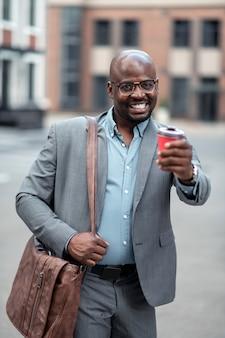 Avoir de la bonne humeur. homme d'affaires portant des lunettes buvant du café du matin et ayant de la bonne humeur
