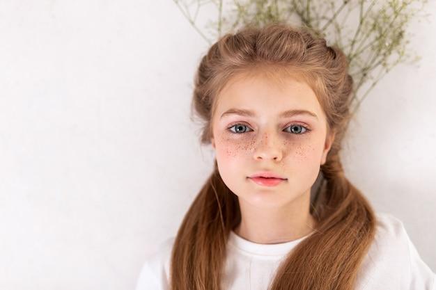 Avoir les cheveux attachés. jolie petite fille au visage mignon allongé sur le sol avec des fleurs et levant les yeux avec de grands yeux bleus