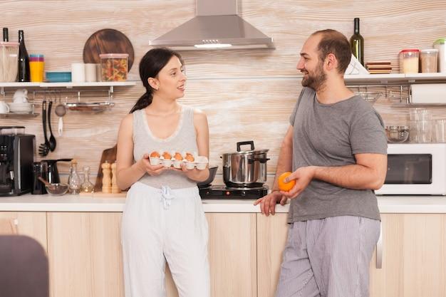 Avoir une conversation le matin dans la cuisine, la femme tenant les œufs et le mari tenant une orange appuyée sur des meubles.