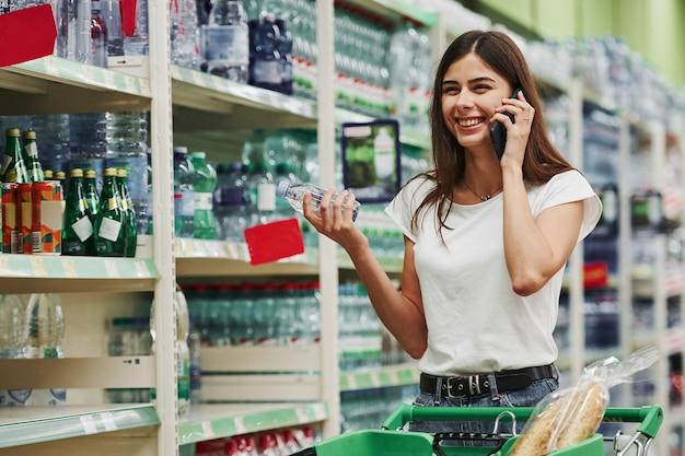 Avoir une conversation en utilisant le téléphone. une acheteuse en vêtements décontractés sur le marché à la recherche de produits.