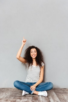 Avoir une idée! jolie femme aux cheveux noirs assis avec les jambes croisées sur le sol mettant l'index vers le haut ce qui signifie eureka sur mur gris