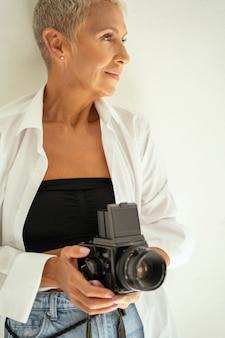Avoir une idée. jolie femme gardant le sourire sur son visage tout en se préparant pour une séance photo
