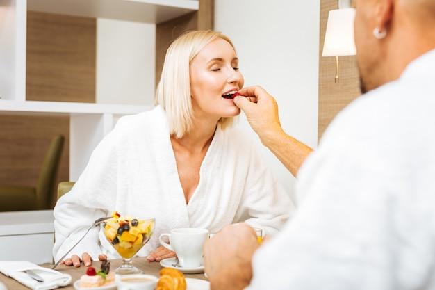 Avoir un petit déjeuner agréable. homme avec boucle d'oreille dans une oreille nourrir sa belle petite amie avec des baies fraîches