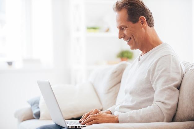 Avoir la possibilité de travailler n'importe où. vue latérale d'un homme mûr travaillant sur un ordinateur portable et souriant assis sur le canapé à la maison
