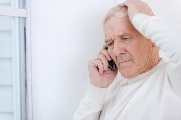 Avoir quelques ennuis. homme senior frustré parlant au téléphone portable et touchant sa tête en se penchant contre le mur