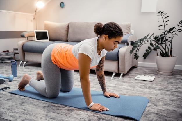 Avoir une session sportive. femme à la peau foncée avec les cheveux attachés se penchant sur le dos pendant la prise d'exercices dans des appartements à la mode modernes