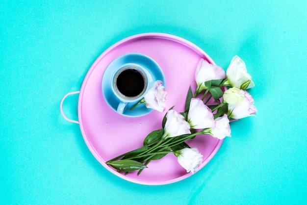 Avoir une tasse de café, des fleurs eustoma sur un plateau sur une surface bleue, un espace de copie plat.