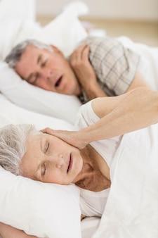 Awake senior femme au lit couvrant ses oreilles pendant que son mari ronfle