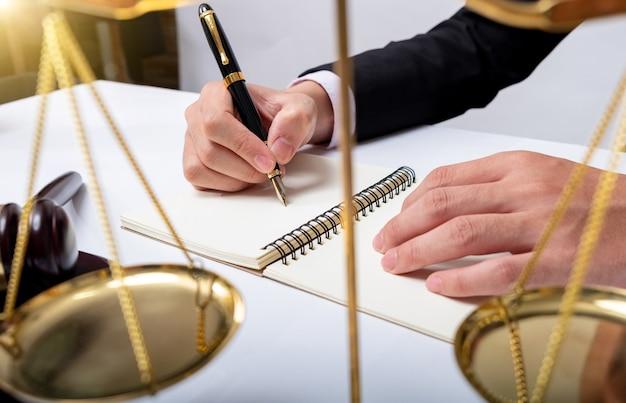 Awyer détail d'un juge assis à son bureau, étudiant de nouvelles lois et législations et prenant des notes. mise au point sélective.