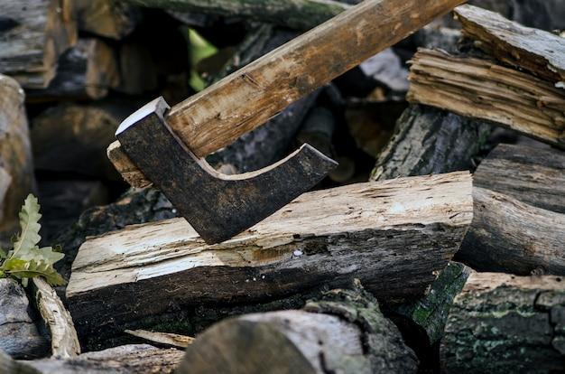 Axe coincé dans une bûche de bois. vieille hache usée, griffée, tranchante, debout sur une souche de bois