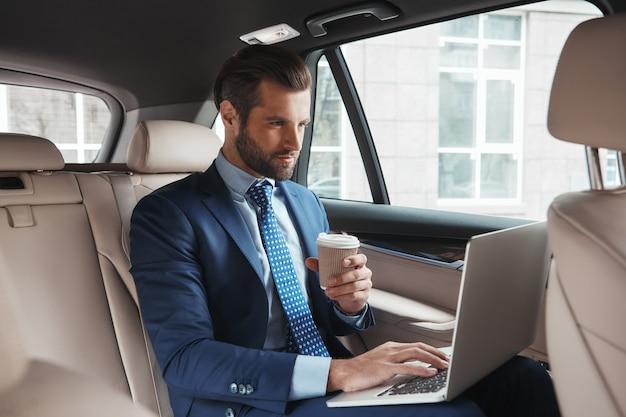 Axé sur le travail jeune homme d'affaires occupé en tenue de soirée travaillant sur un ordinateur portable et buvant chaud
