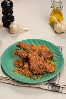 Ayam serundeng, recette de poulet frit traditionnel indonésien avec noix de coco râpée.