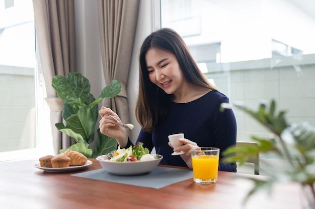 Ayant le concept de repas une jolie femme mélangeant une vinaigrette sans calories avec une salade verte dans le bol.