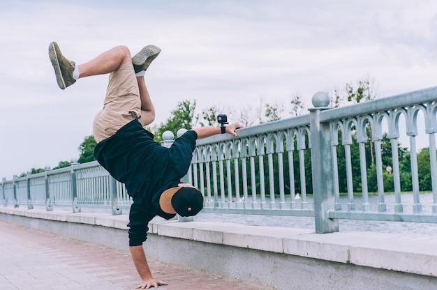 B-boy break dancer se tient sur un bras avec une caméra d'action.