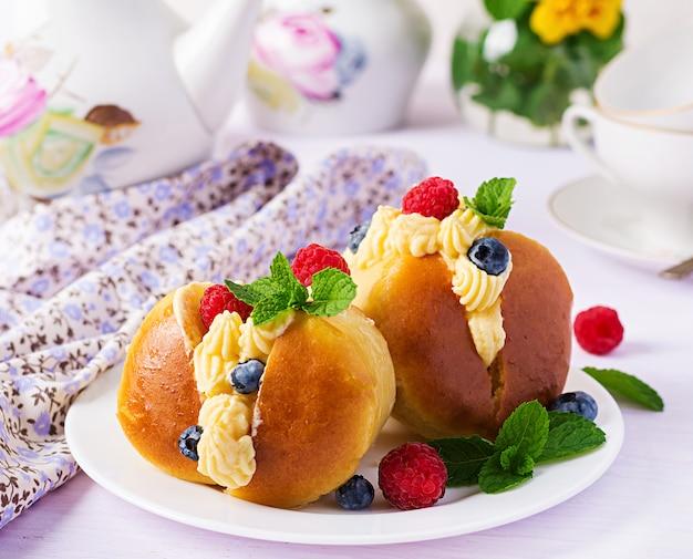 Baba au rhum décoré de crème fouettée et de framboises et myrtilles fraîches. savarin au rhum, crème et baies