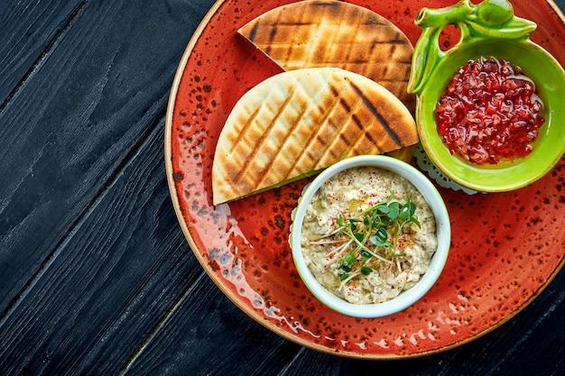 Baba ghanoush traditionnel israélien ou oriental avec salsa de légumes et pita, servi dans une assiette rouge sur une table en bois