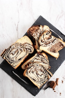 Babka au chocolat ou pain brioché. pâtisserie du désert sucrée maison - pain tourbillon au chocolat avec texture marbrée. tranché sur fond blanc