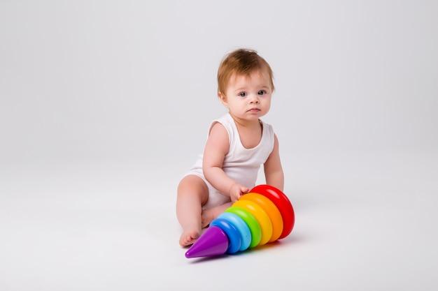 Baby sitting jouant avec un jouet éducatif sur fond blanc