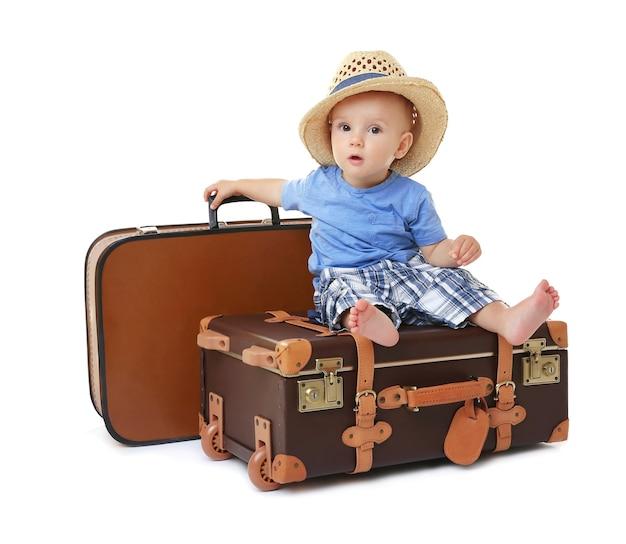 Baby sitting sur valise sur fond blanc