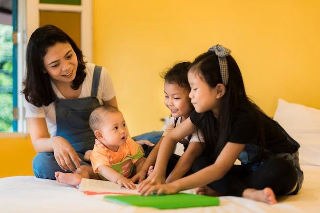Babysitting jouer avec trois enfants espiègles et espiègles portant sur le lit.