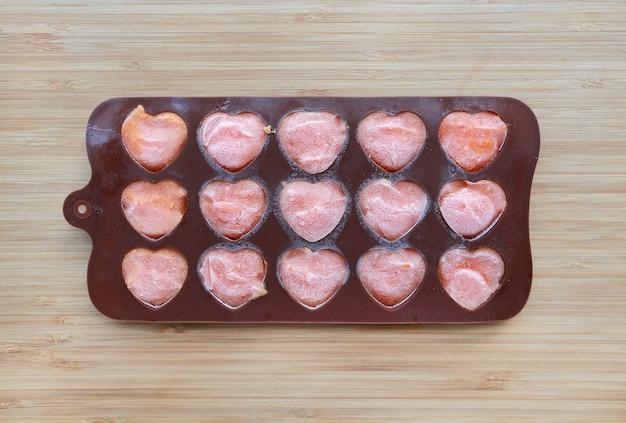 Bac à glaçons avec légumes surgelés sur planche de bois, congelez les carottes en purée.