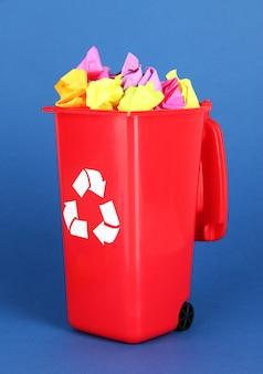 Bac de recyclage avec des papiers sur bleu