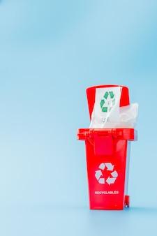 Le bac de recyclage rouge sur fond bleu