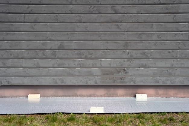 Bâche au sol à côté du mur du bâtiment.