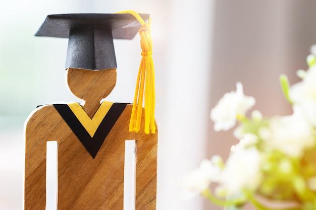 Back to school people signer du bois avec le bonnet de graduation célébrant avec une fleur