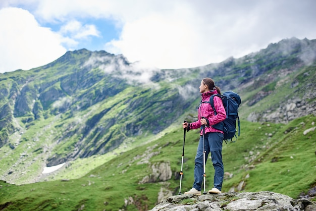 Backpacker femme se reposant pendant la randonnée debout au sommet d'un rocher bénéficiant d'un paysage de montagne fantastique autour