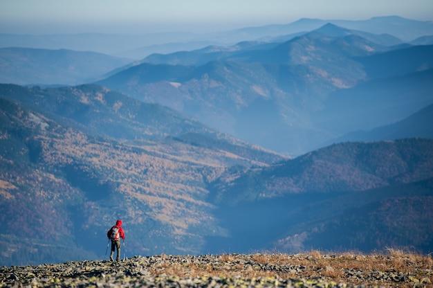 Backpaker mâle marchant sur le sommet rocheux de la montagne