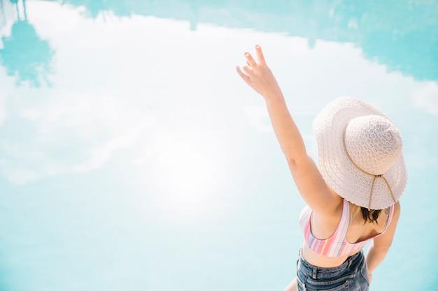Backview de femme posant devant la piscine