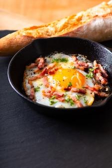 Bacon au fromage et oeuf au plat dans une poêle en fonte avec espace pour copie