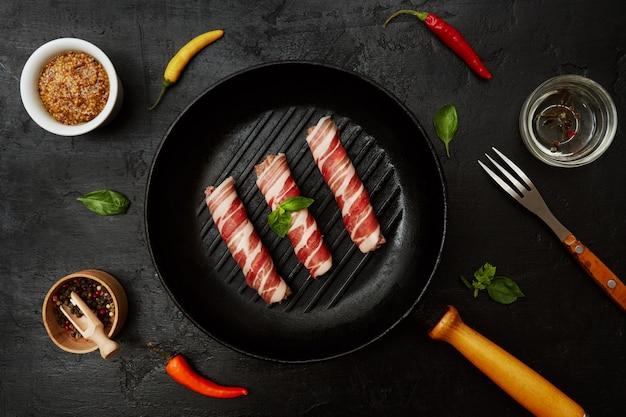 Bacon cru roule dans une poêle à frire avec des herbes, une fourchette et de la moutarde. espace de copie vue de dessus.