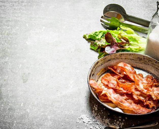 Bacon dans une poêle avec du sel et des herbes. sur un fond de pierre.