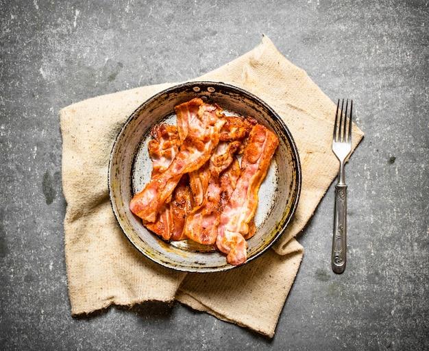 Bacon frit dans une poêle sur le tissu. sur un fond de pierre.