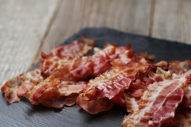 Bacon frit sur plaque de pierre noire