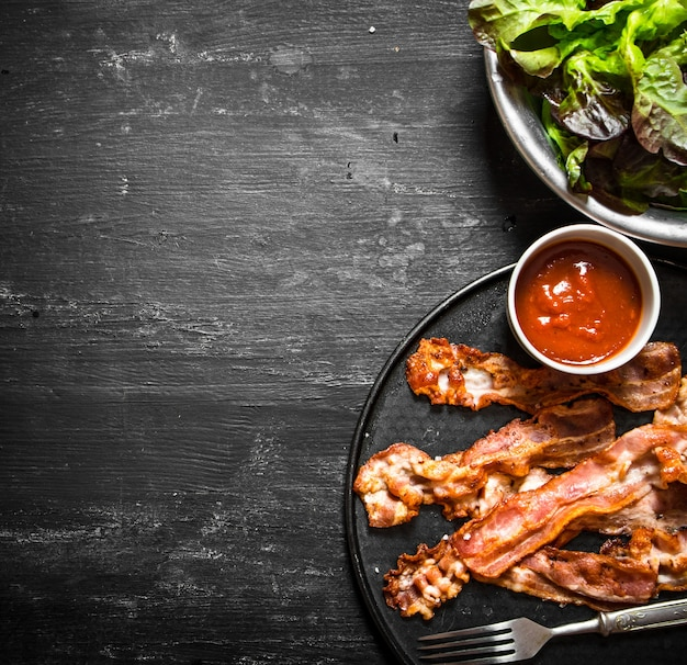 Bacon frit avec sauce et légumes verts sur fond de bois noir