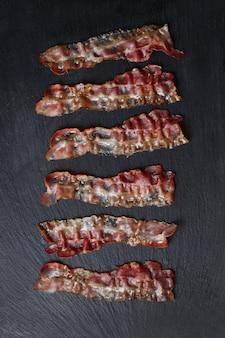 Bacon frit sur table en pierre noire