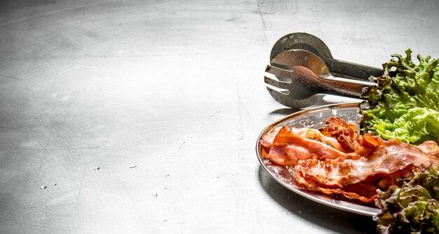 Bacon frit avec des verts sur la table en métal