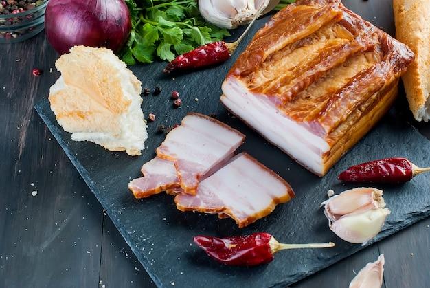 Bacon fumé à la baguette et légumes sur tableau noir pierre
