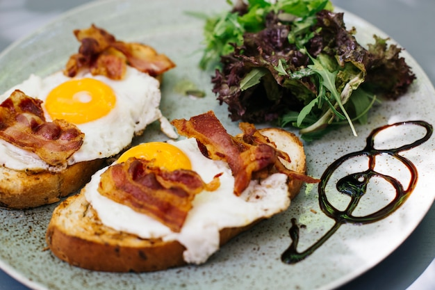Bacon et œufs au plat sur pain grillé avec décoction de laitue