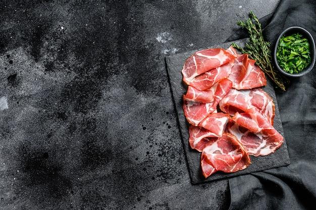 Bacon roulé italien pancetta piacentina. la viande de porc. fond noir.